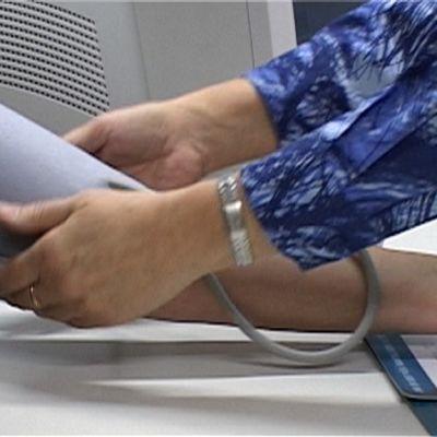 Hoitaja mittaa koululaisen verenpainetta.