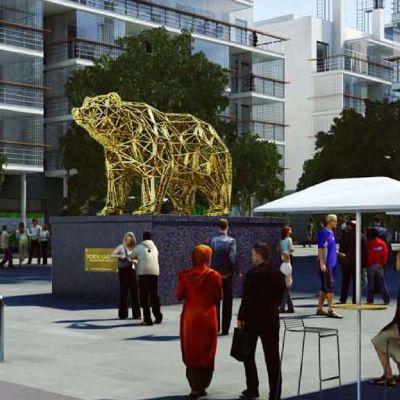 Kultainen karhu aukiolla kerrostalojen keskellä.