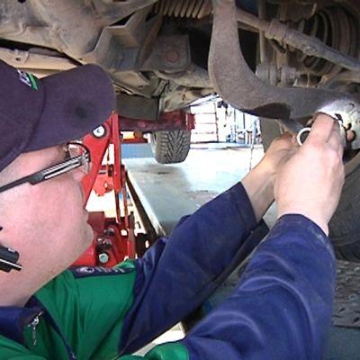 Kuvassa katsastaja tarkistaa henkilöauton renkaan kiinnitysjärjestelmää