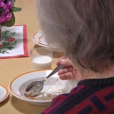 Vanhus syö aamupalaa: puuroa ja leipää.