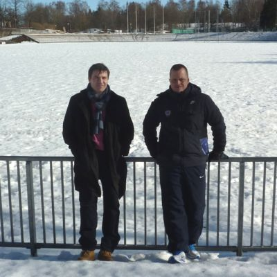Miehet nojaavat aitaan lumisen jalkapallokentän laidalla.