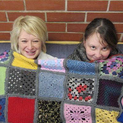 Opettajat Kati Laine ja Minna Koskela istuvat opettajahuoneen sohvalla torkkupeiton alla
