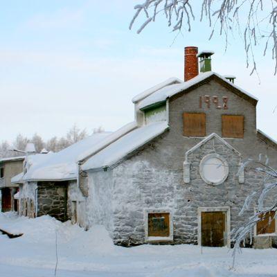 Vanha harmaa kivinen Kiteen meijerirakennus.