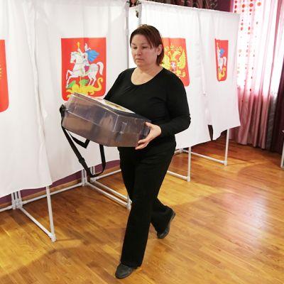 Vaalivirkailija kantaa laatikkoa.