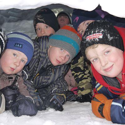 Seitsemän poikaa kurkistaa Pingu-leirillä rakennetun lumi-iglun oviaukosta