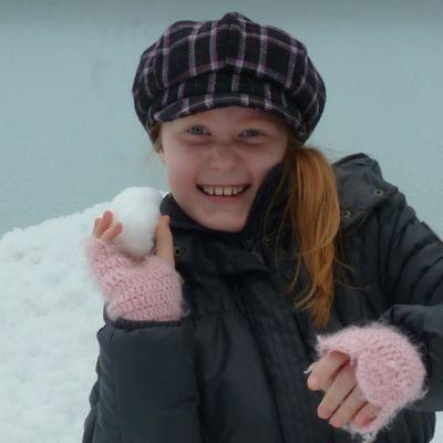 tyttö heittää lumipalloa