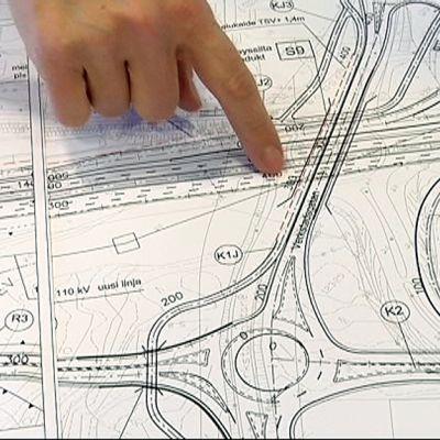 Suunnitelman luonnos paperilla. Sormi osoittaa tien merkintää.