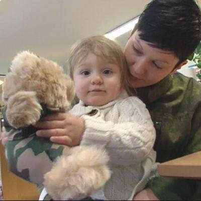Varusmiespalveluksessa oleva nainen pitää lasta sylissään.