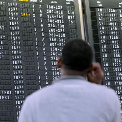 Mies tarkastelee lähtevien lentojen muutoksia Frankfurtin lentokentällä.