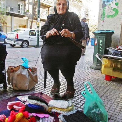 Nainen istuu tuolilla kutomassa, maassa viltin päällä kudottuja lakkeja ja lapasia.