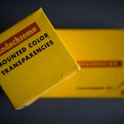 Kaksi vanhaa Kodakin keltaista diasäilytyslaatikkoa päällekkäin. Alempi, leveämpi laatikko näkyy epäselvänä taustalla.