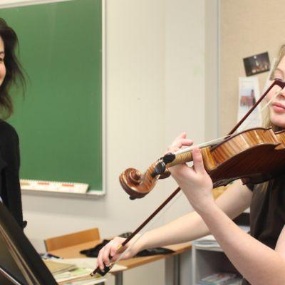 Kuvassa tyttö soittaa viulua opettajansa opastuksella