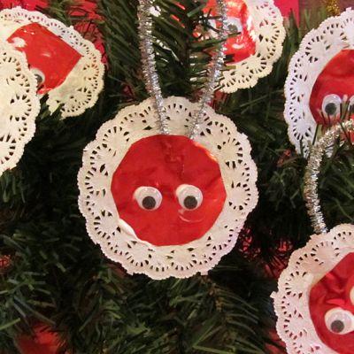 Kuusesta riippuu paperista leikattuja punaisia ympyröitä joissa on silmät ja pitsireunukset.