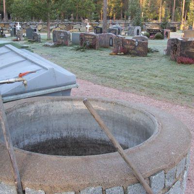 Kuvassa hautausmaa, hautakiviä, vesiäiliö ja jätepönttö