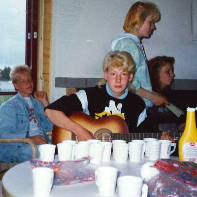 Poika soittaa kitaraa. Pöydällä paljon pahvimukeja.