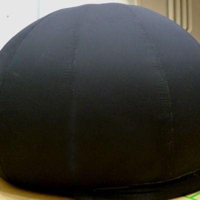 Musta planetaario koulun liikuntasalissa.