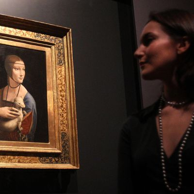 Galleriatyöntekijä katselee Leonardo da Vincin maalaamaa Cecilia Galleranin muotokuvaa.