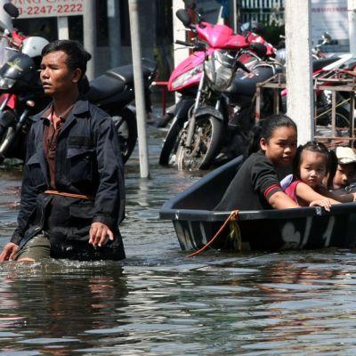Mies kahlaa vedessä ja vetää perässään sammiota jossa on hänen perheensä.