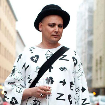 Kuvassa mies joka pitelee shampanjalasia keskellä katua.