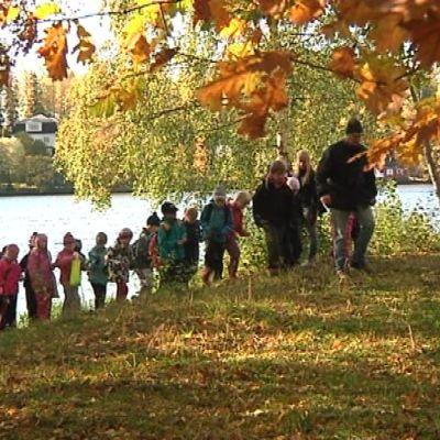aikuisia ja lapsia kävelee syksyisessä metsässä