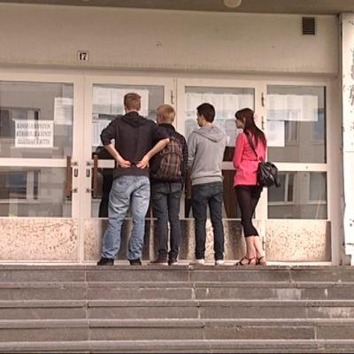 Voionmaan lukion oppilaat katsovat yo-kokeiden tuloksia koulun ovesta.