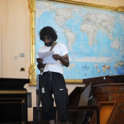 Kapinallissotilas lukee papereita, joita löytyi Muammar Gaddafin pojan, Al-Saadin, asunnosta.