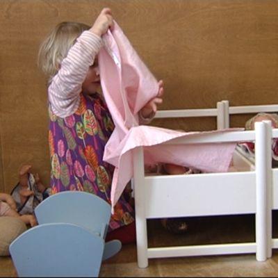 Lapsi leikkii nukeilla.