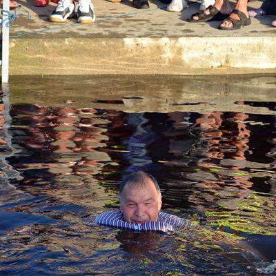 Kuvassa Ralf Sundberg veteen heitettynä. Taustalla näkyy laiturin reunaa ja sillä seisovien ihmisten jalkoja.