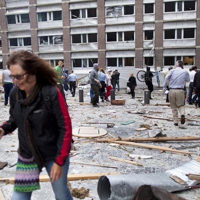 Ihmiset kävelevät räjähdyksen levittämän rojun keskellä hallituskorttelin kaduilla.
