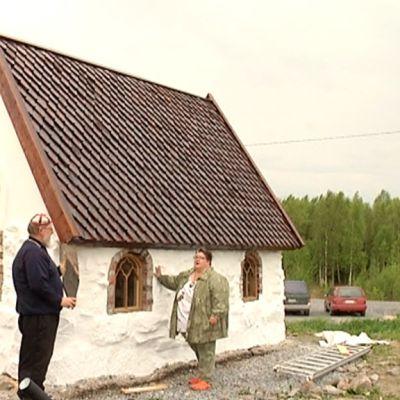 Kuvassa Martti Nykänen ja Leena Harjunpää Suomen pienimmän kivikirkon luona