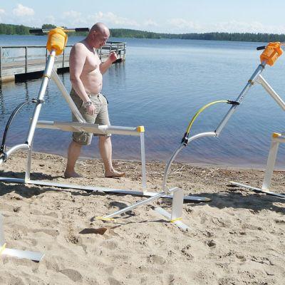 Kuvassa kaksi miestä rannalla kokoamassa waterbird-laitetta