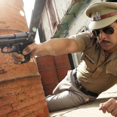 Elokuvan korruptoitunut poliisi tähtää aseella.