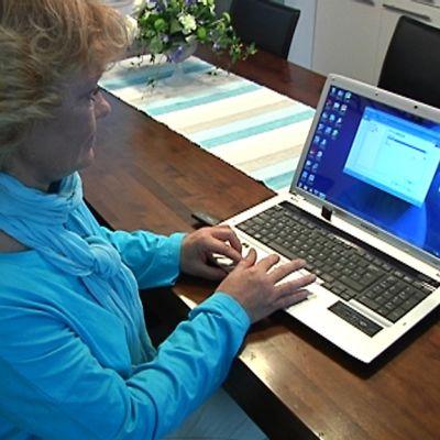 Kuvassa on Perhon ATK-vastaava Tarja Sillanpää kannettavan tietokoneen ääressä.