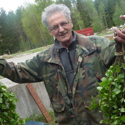 Jouko Mäki-Petäjä pitelee kahta saunavihtaa.