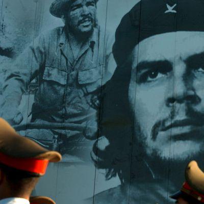 Suuri valokuva Chestä, edessä ohi marssivien sotilaiden lakkeja.