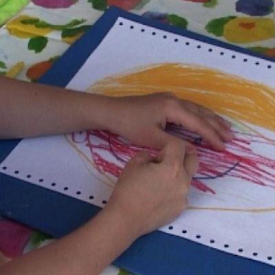 hellehattuinen lapsi piirtää