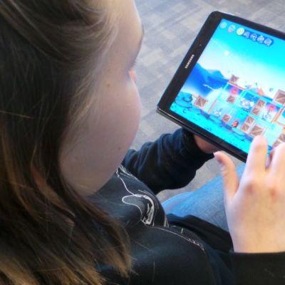 tyttö pelaa mobiilipeliä