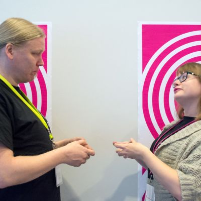 Northern Game Summit -pelinkehityskonferenssin tapahtumamanageri Emma Karttunen ja tapahtumatuottaja Tommi Krogerus esittävät pelaavansa vastakkain toisiaan.