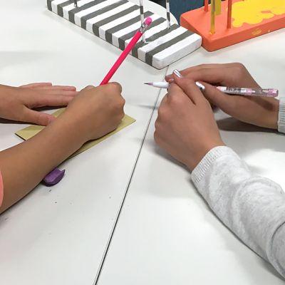 Oppilaiden kädet pöydällä