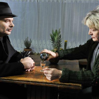Hienosti pukeutunut, mustahattuinen mies ja iäkäs nainen istuvat ravintolan pöydässä. Nainen kaataa pikariin pientä ryyppyä.
