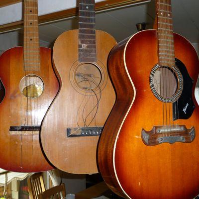 Useita akustisia kitaroita roikkuu telineessä.