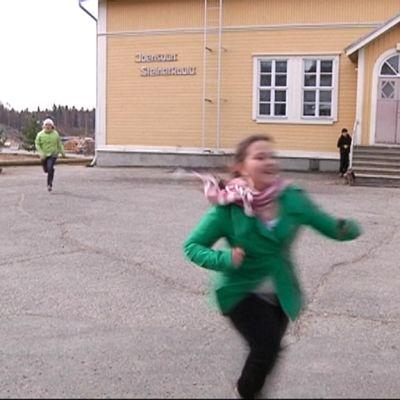 Tyttö juoksee koulun pihalla.