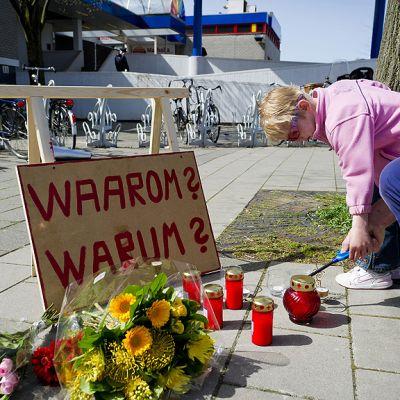 Ihmiset tuovat kukkia ja kynttilöitä ostoskeskuksen ulkopuolelle.