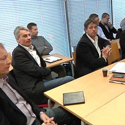 Kansainvälisen yritysryppään edustajia pöydän ääressä.