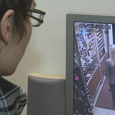 Kultaliikkeen toimitusjohtaja tarkkailee valvontakameraa takahuoneessa.