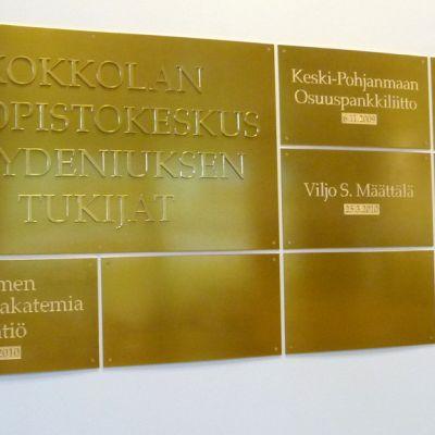 Kuvassa kunniataulu, jossa on yliopistokeskukselle rahaa lahjoittaneiden yritysten, yhteisöjen ja yksityisten nimiä.