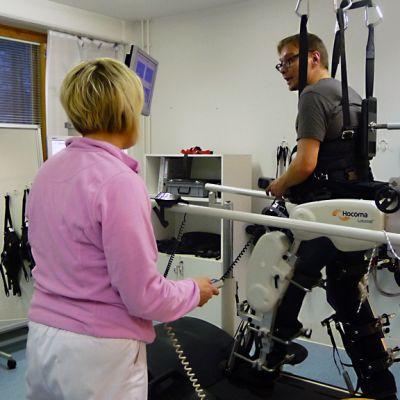 Toimittaja Petri Kuikka testaa kävelyrobottia.