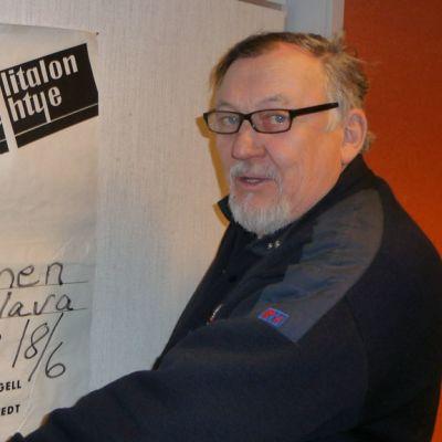 Kuvassa Alpo Ylitalo ja vanha juliste hänen yhtyeensä Kannuksen-keikasta.