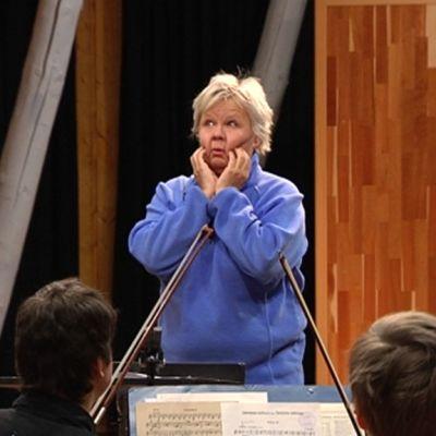 Näyttelijä Ulla Tapanien johtaa orkesteria.
