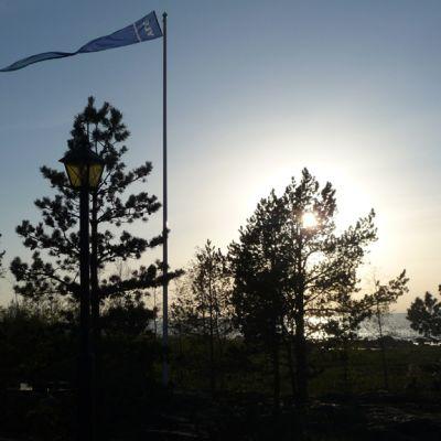 Kuvassa auringonlaskua vasten merenrannalla oleva lipputanko. Tangossa liehuu isännänviiri.